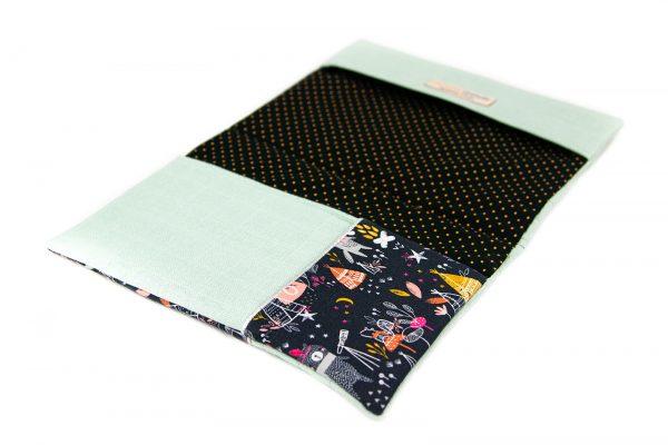 Vu de biais du protège carnet de santé en lange vert d'eau et tissu imprimé tipi et renard, ouvert et à plat.