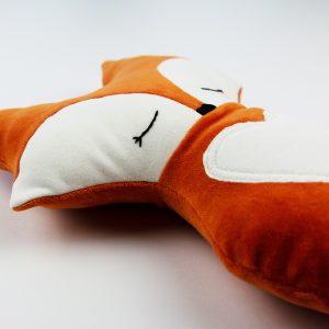 Doudou renard endormi, couleur citrouille, vu de biais.